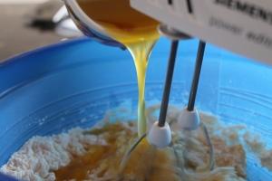 zerlassene Butter während des Rührens zum Teig geben.